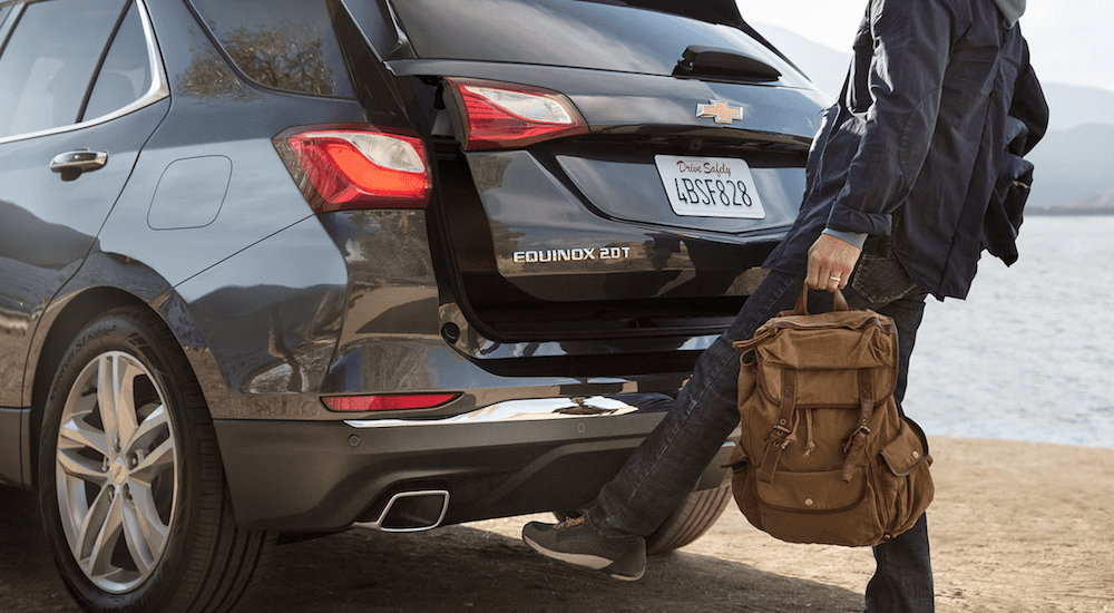 A man waves his foot to open the power liftgate on a black 2019 Chevy Equinox at the beach