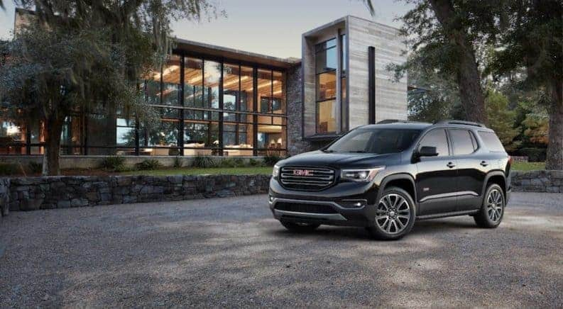 A black 2019 GMC Acadia All Terrain in front of a modern glass building