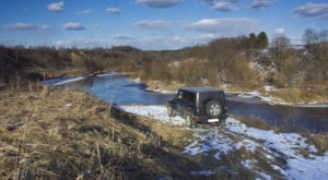 A black Jeep Wrangler in a river