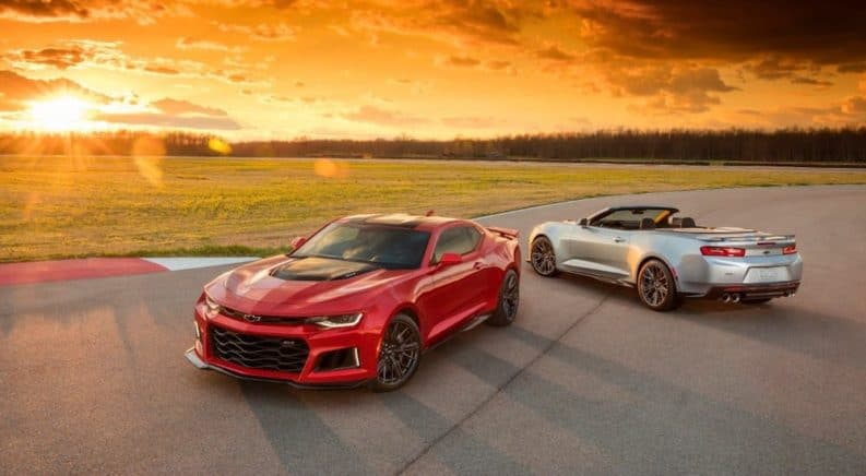 Red and silver 2019 Chevy Camaros on a track at sunset