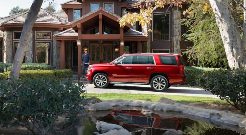A red 2019 Chevy Tahoe rests easy in front of a mansion when it comes to 2019 Chevy Tahoe vs 2019 Ford Expedition