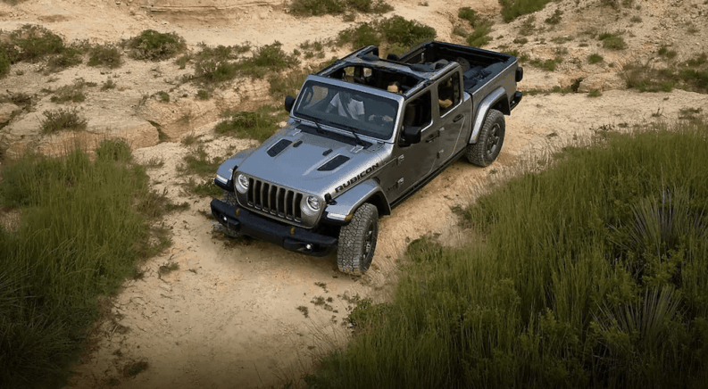 A gray 2020 Jeep Gladiator treks through the desert with the top down
