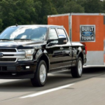 Black used ford truck towing an orange trailer