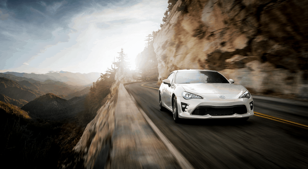 A white 2019 Toyota 86 sports car is driving a road along a cliff edge.