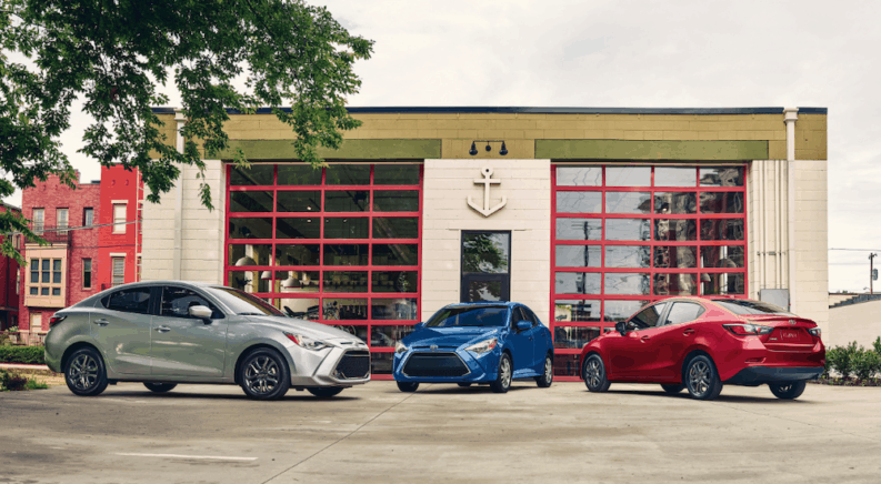 A silver, a blue, and a red 2019 Toyota Yaris sparked outside a garage in a city.