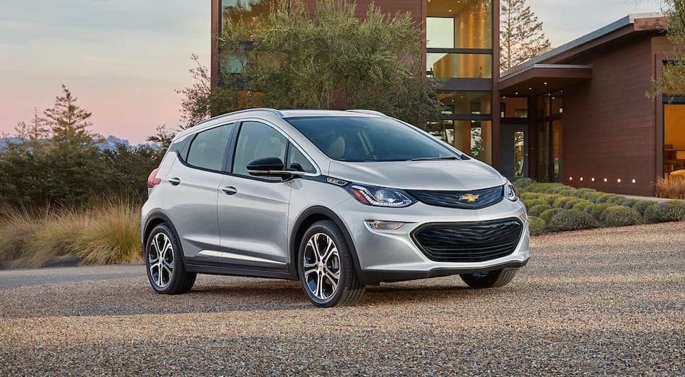 A silver 2019 Chevy Bolt is parked in the driveway of a modern house. It is one of the current Chevy cars offered.