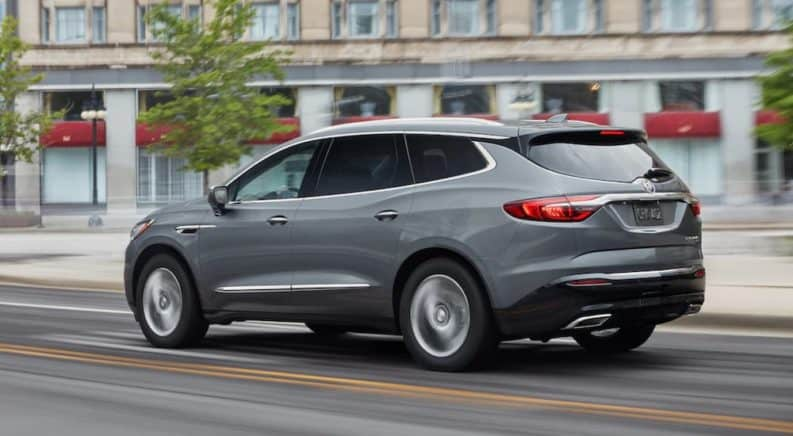 A grey 2019 Buick Enclave is driving past a city building.