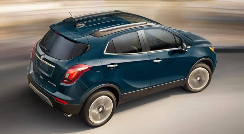 A blue 2019 Buick Encore is driving with a blurred background.