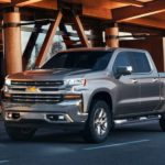 A silver 2019 Chevy Silverado 1500 is parked in front of a wood and glass building.