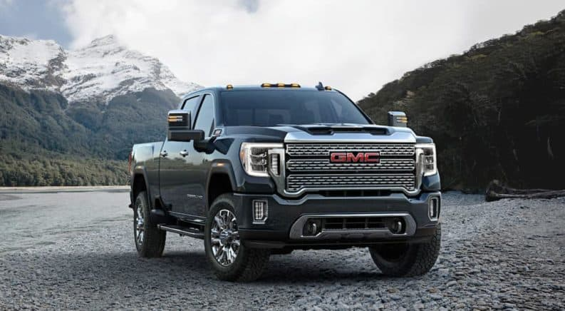A grey 2020 GMC Sierra 2500HD Denali is parked with snowy mountains in the distance.