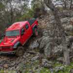 The 2020 Jeep Gladiator is shown driving down a rock hill in the woods.
