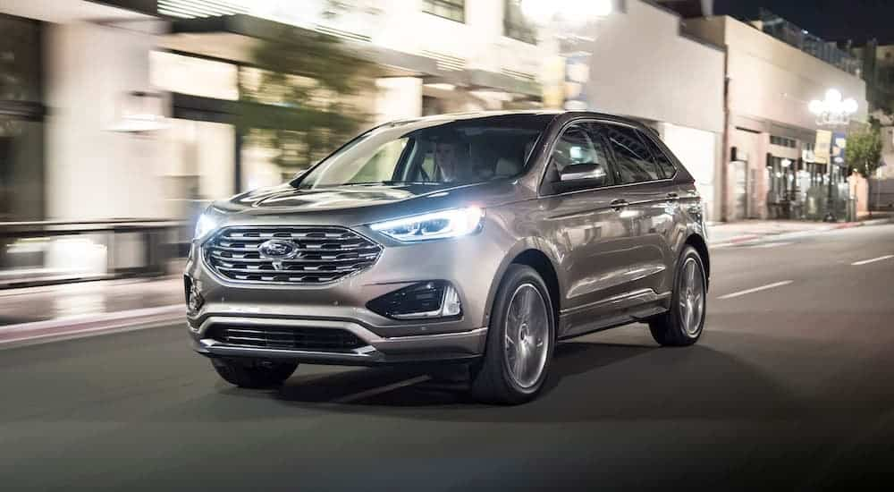 A tan 2019 Ford Edge is driving down a city street at night.