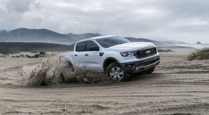 A white 2019 Ford Ranger is driving in the sand. Check out base level performance when comparing the 2019 Ford Ranger vs. 2019 Chevy Colorado.
