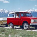A red 1966 Ford Bronco is towing a popup camper in front of mountains.