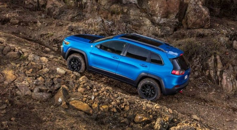A blue 2019 Jeep Cherokee is climbing a rocky trail.