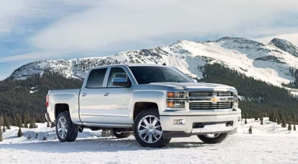 A white 2014 Chevy Silverado, a popular choice for used trucks for sale, is parked in the snow in front of mountains.