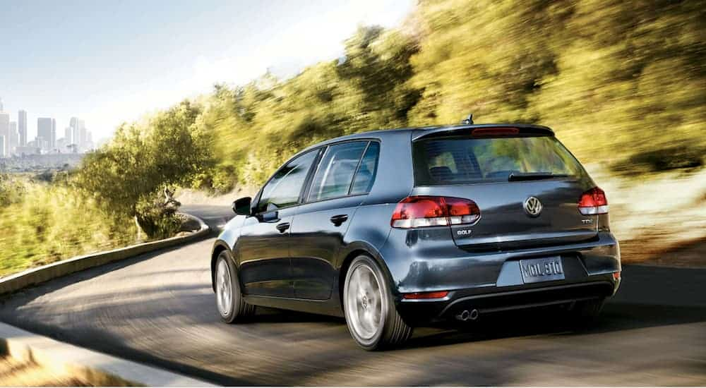 A dark grey 2014 Volkswagen Golf TDI is driving towards a city skyline on a winding road.