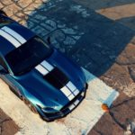 A blue 2020 Shelby GT500 with white stripes is on an old race track.
