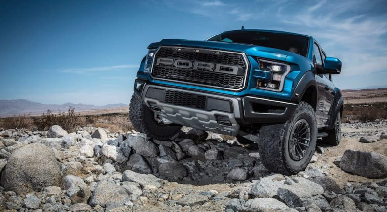 A blue 2019 Ford Raptor is on a rocky trail.