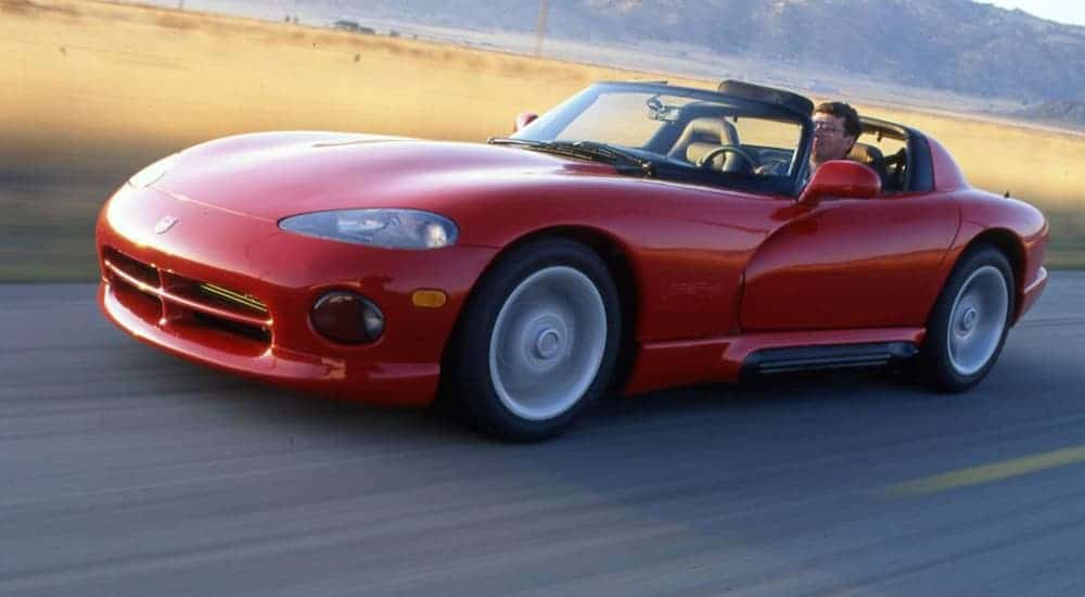 A red 1992 Dodge Viper is driving on road past a grassy field.