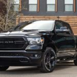 A black 2020 Ram 1500, which wins when comparing the 2020 Ram 1500 vs 2020 Ford F-150, is parked in front of a wooden wall next to a house.