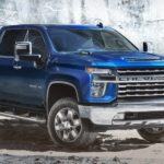 A blue 2020 Chevy Silverado 2500 HD is parked in front of a rock wall near a Chevy dealership.