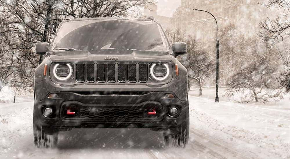 A grey 2020 Jeep Renegade, which wins when comparing the The 2020 Jeep Renegade vs the 2020 Hyundai Kona, is driving on a snow covered road during a snow storm.