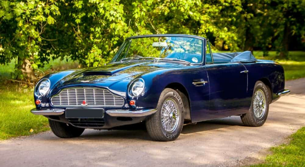 A blue 1968 Aston Martin DB6 Volante is parked next to a tree in the sun.