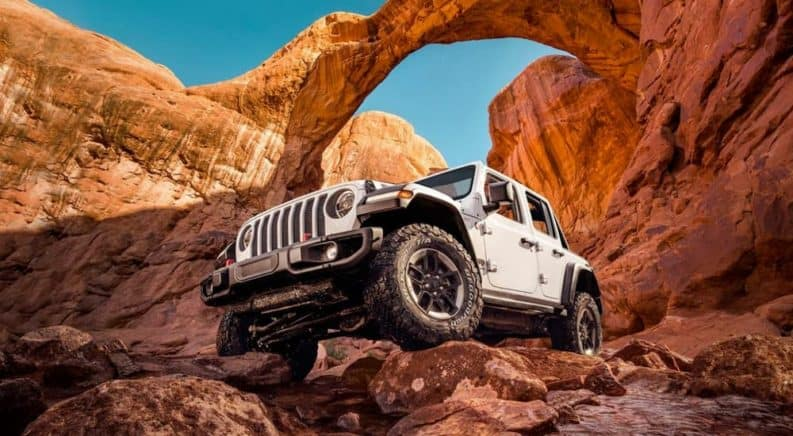 A white 2020 Jeep Wrangler, which wins when comparing the 2020 Jeep Wrangler vs 2020 Jeep Gladiator, is off-roading in a red rocks canyon.