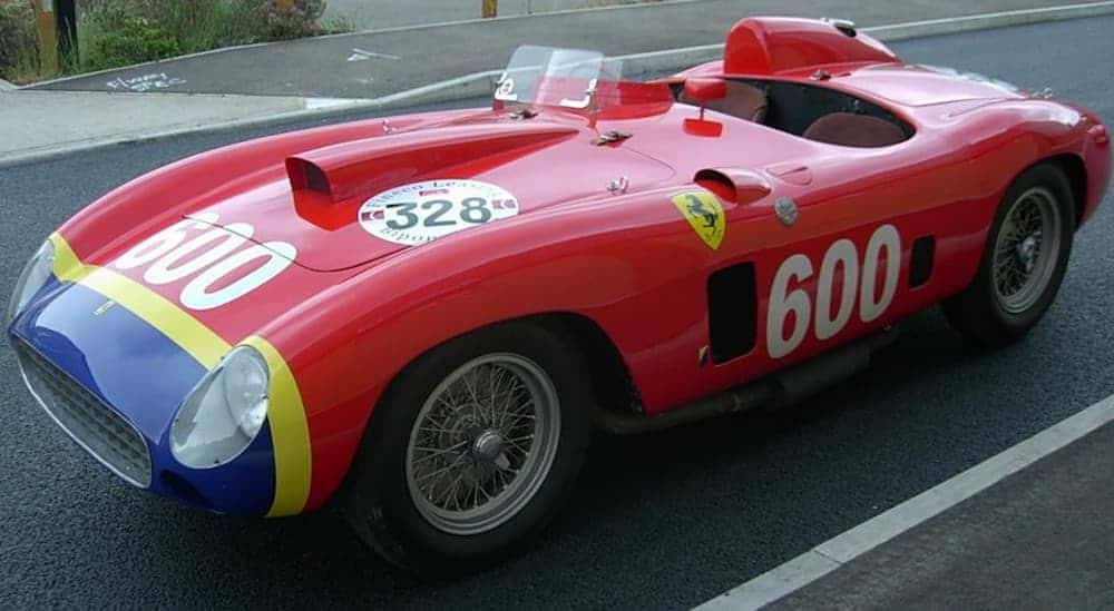 A red, with race number decals on it, 1956 Ferrari 290 MM is parked in an empty parking lot.