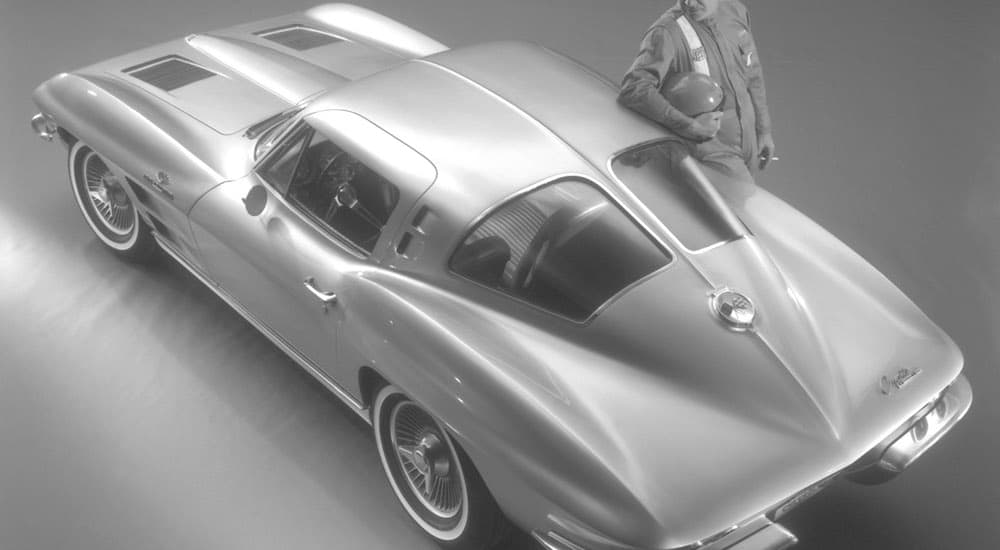 A race car driver is leaning on a 1963 Chevy Corvette, shown in black and white.