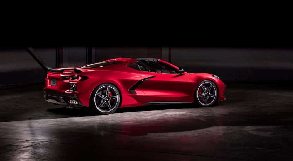 A red 2020 Chevy Corvette is parked in a dark lit garage.