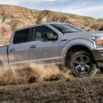 A silver 2020 Ford F-150, which wins when comparing the 2020 Ford F-150 vs 2020 Toyota Tundra, is off-roading with desert hills behind it.