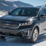 A grey 2020 Kia Sorento is driving on a snow covered road with snow covered mountains in the distance.