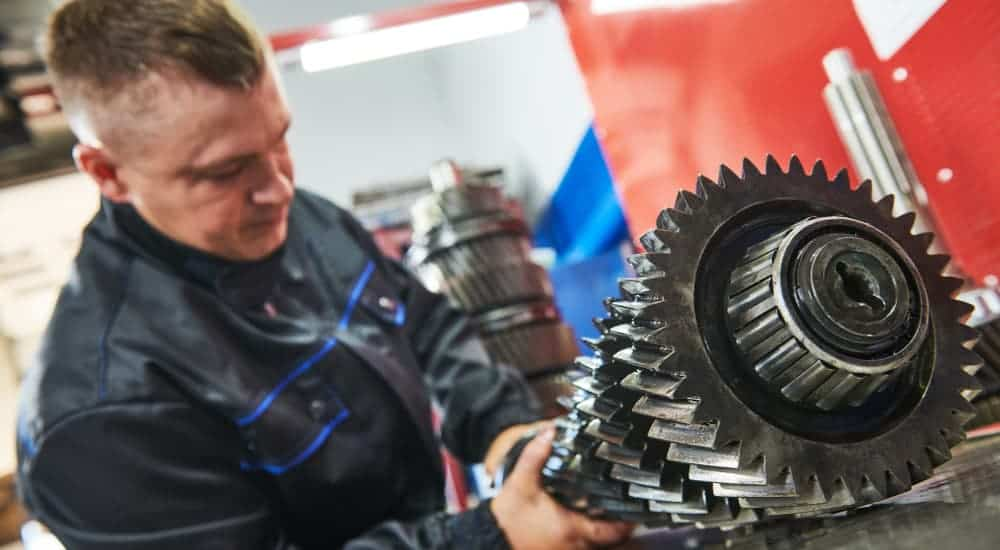 A mechanic is working on new gears for a lifted truck.