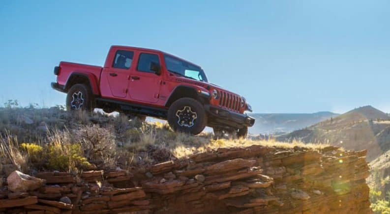 A red 2020 Jeep Gladiator is on a rocky ledge that's overlooking a valley.