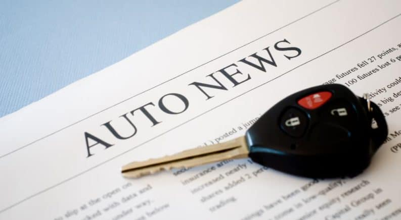 """A newspaper that says """"Auto News"""" with a car key on it is shown."""
