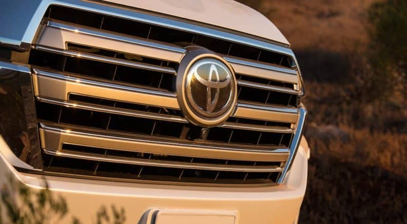 A close up of the Toyota logo on a white Toyota SUV is shown.