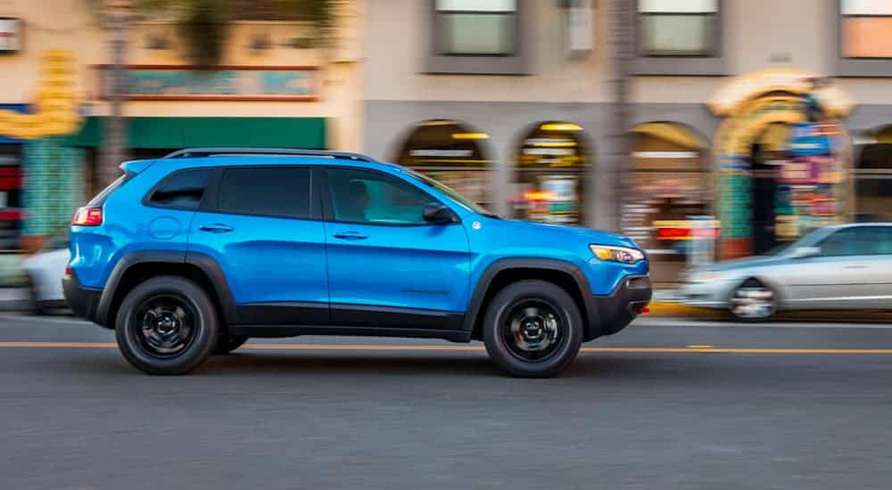 A blue 2020 Jeep Cherokee is driving downtown.