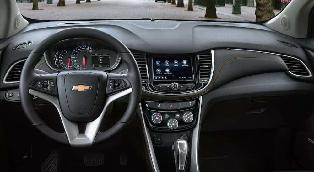 The front black leather interior of a 2020 Chevy Trax is shown.