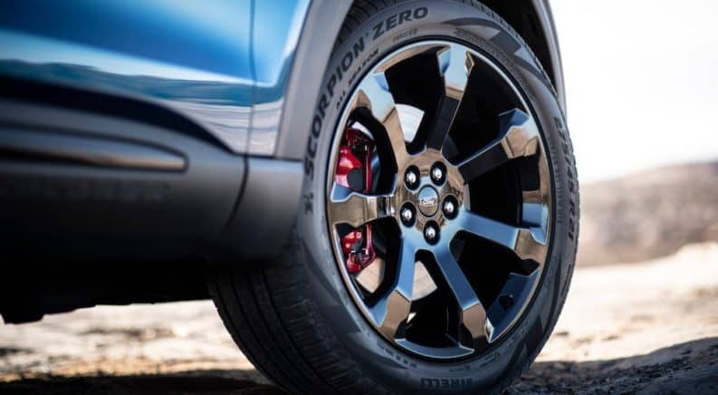 A closeup is shown of a wheel on a blue 2020 Ford Explorer.