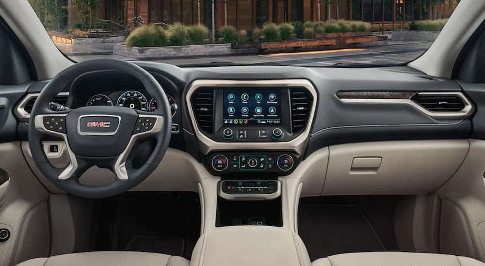 The front tan and black leather interior of a 2020 GMC Acadia is shown.