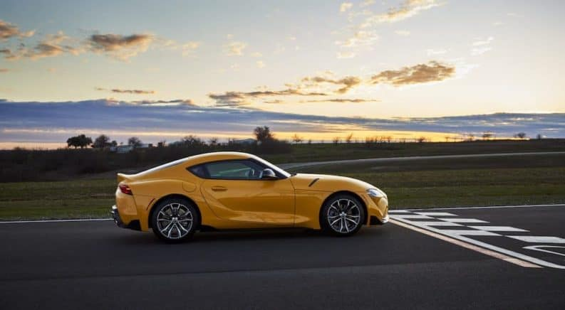 In current auto news, the 2021 Toyota Supra is taking off, shown here a yellow Supra is at the finish line of a racetrack.