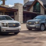 A grey 2020 Chevy Suburban and a white 2020 Chevy Tahoe are parked in front of a large home.