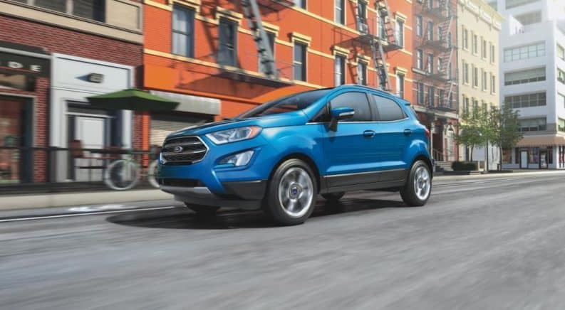 A blue 2020 Ford EcoSport is driving on a city street.