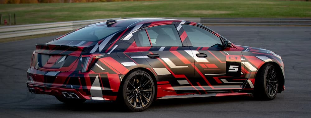 A 2021 Cadillac CT5-V Blackwing with a red, white, and black design on it is racing around a track.