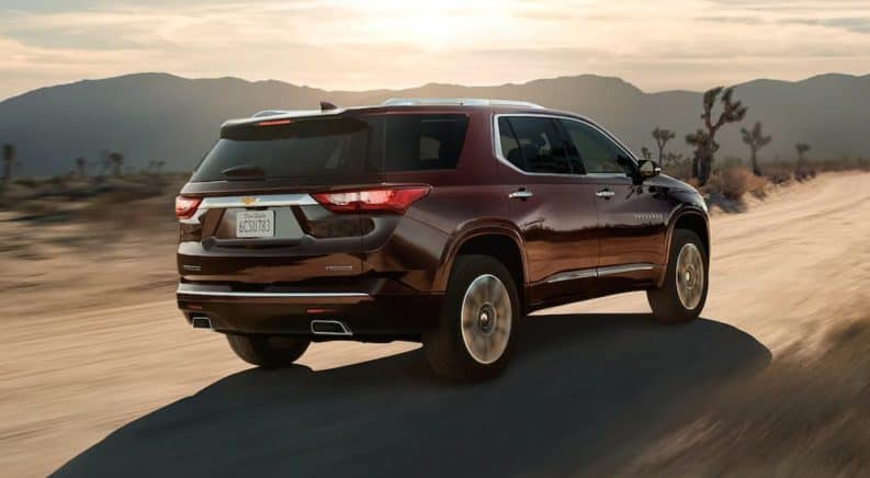 A burgundy 2020 Chevy Traverse is driving on a dirt road in the desert after winning the 2020 Chevy Traverse vs 2020 Ford Explorer comparison.