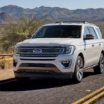 A white 2020 Ford Expedition King Ranch is driving on a desert highway.