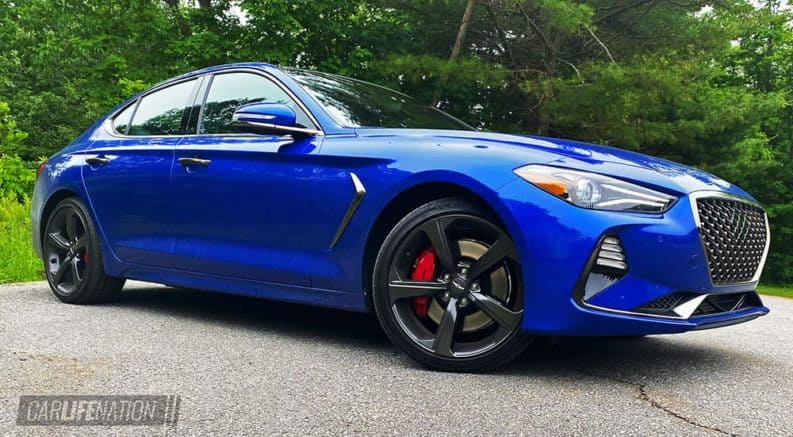 A blue 2020 Genesis G70 is shown parked in front of trees angled to the right.