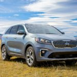 A grey 2020 Kia Sorento is parked in a field in front of mountains after winning the 2020 Kia Sorento vs 2020 Mazda CX-9 comparison.
